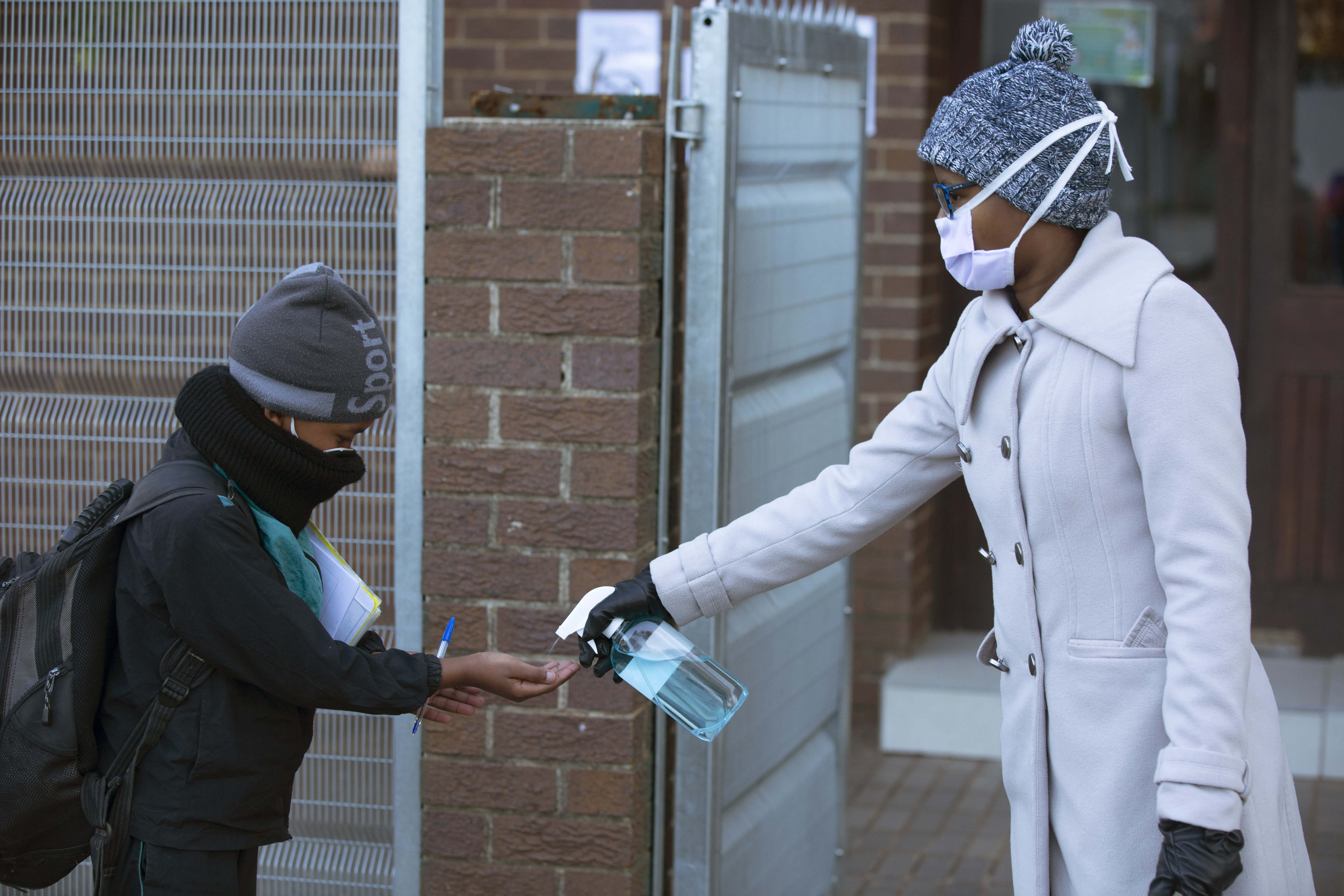 A pupil's hands are sanitised on returning to school in Johannesburg, Monday July 6, 2020, as more learners were permitted to return to class. Schools were shut down in March prior to a total country lockdown in a bid to prevent the spread of coronavirus and are now slowly being re-opened. (AP Photo/Denis Farrell)