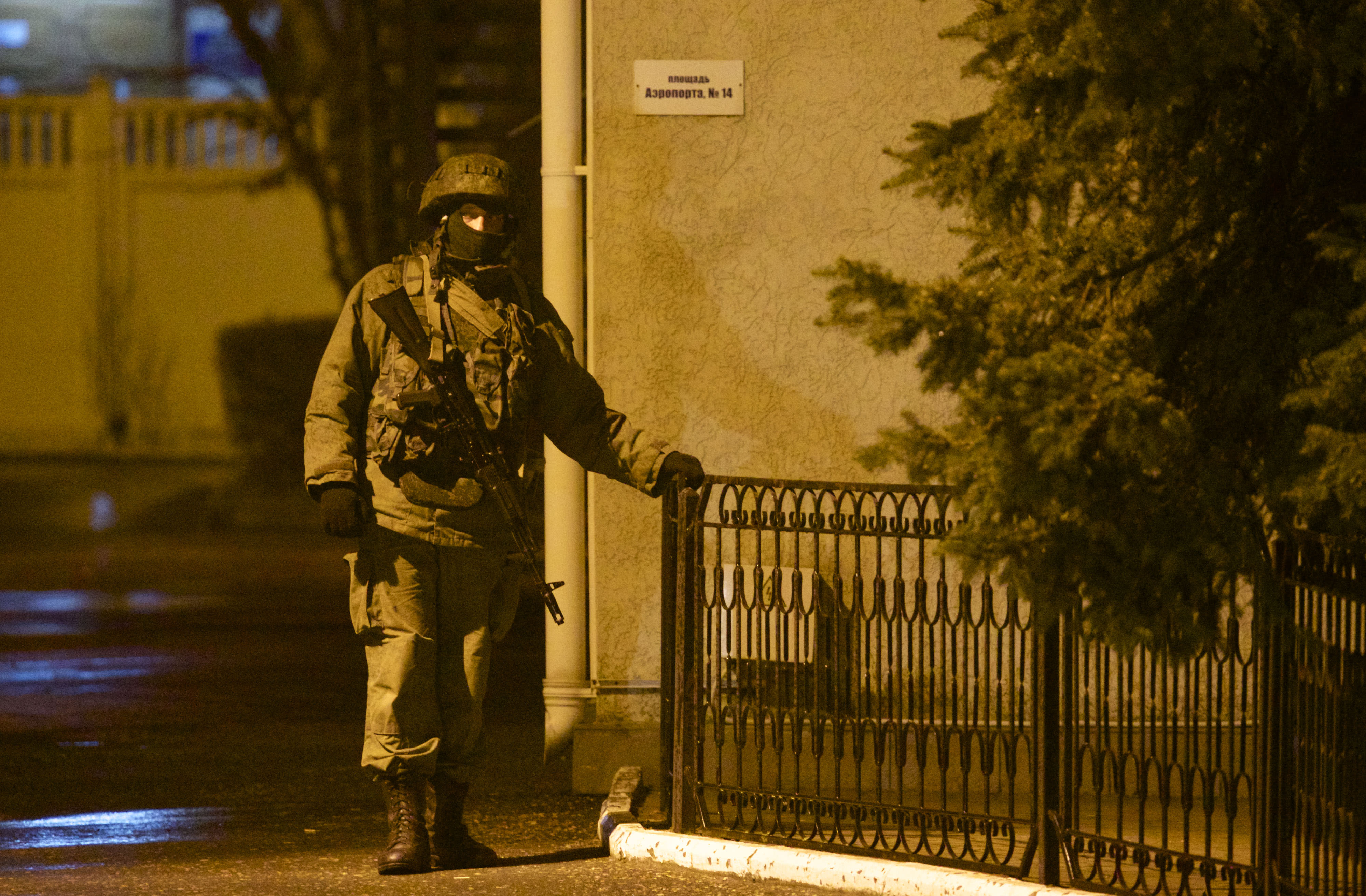 An unidentified armed man guards a building at the airport in Simferopol, Ukraine, Friday, Feb. 28, 2014. Dozens of armed men in military uniforms without markings patroled the airport in the capital of Ukraine's strategic Crimea region. (AP Photo/Ivan Sekretarev)