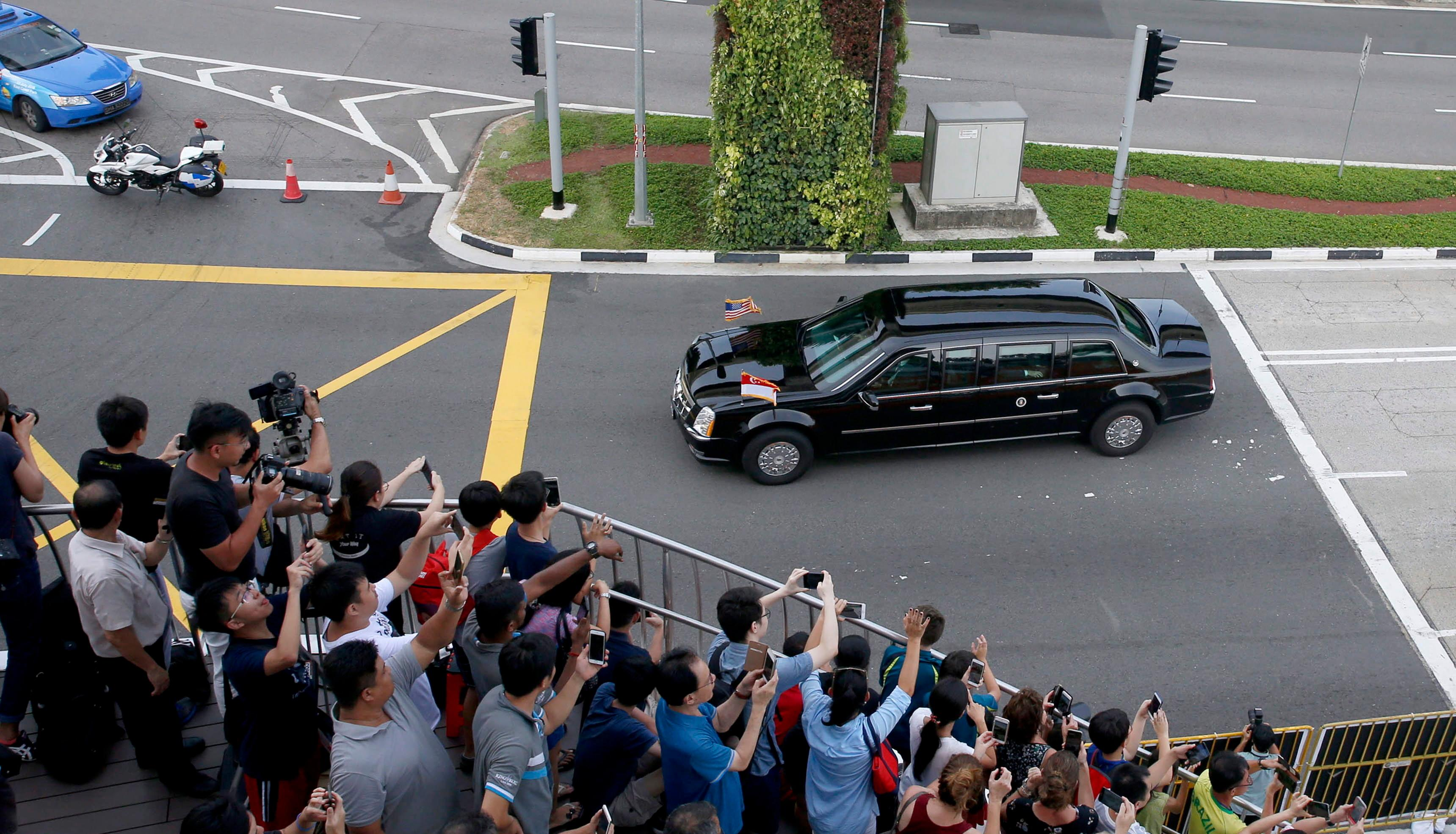 <p>People wave and take photos as the car carrying US President Donald J. Trump leaves Sentosa Island after a historic summit with North Korean leader Kim Jong-un, in Singapore, June 12, 2018. (Photo: Lynn Bo Bo/EPA-EFE/REX/Shutterstock) </p>
