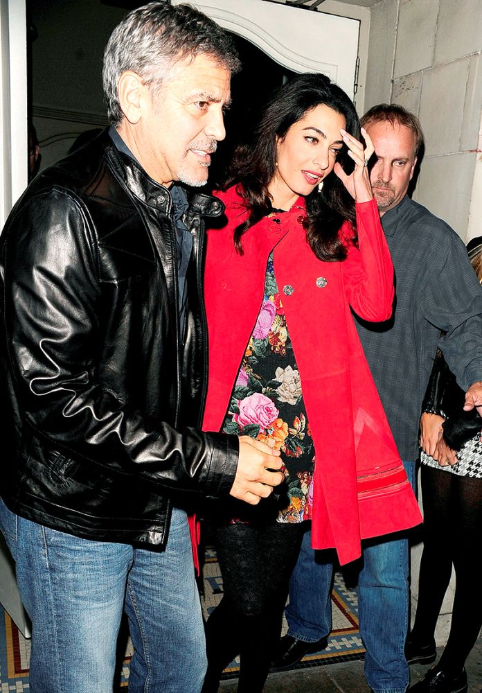 George Clooney and wife Amal try to dodge the cameras on a 2015 date night in London. (Photo: AKM-GSI)