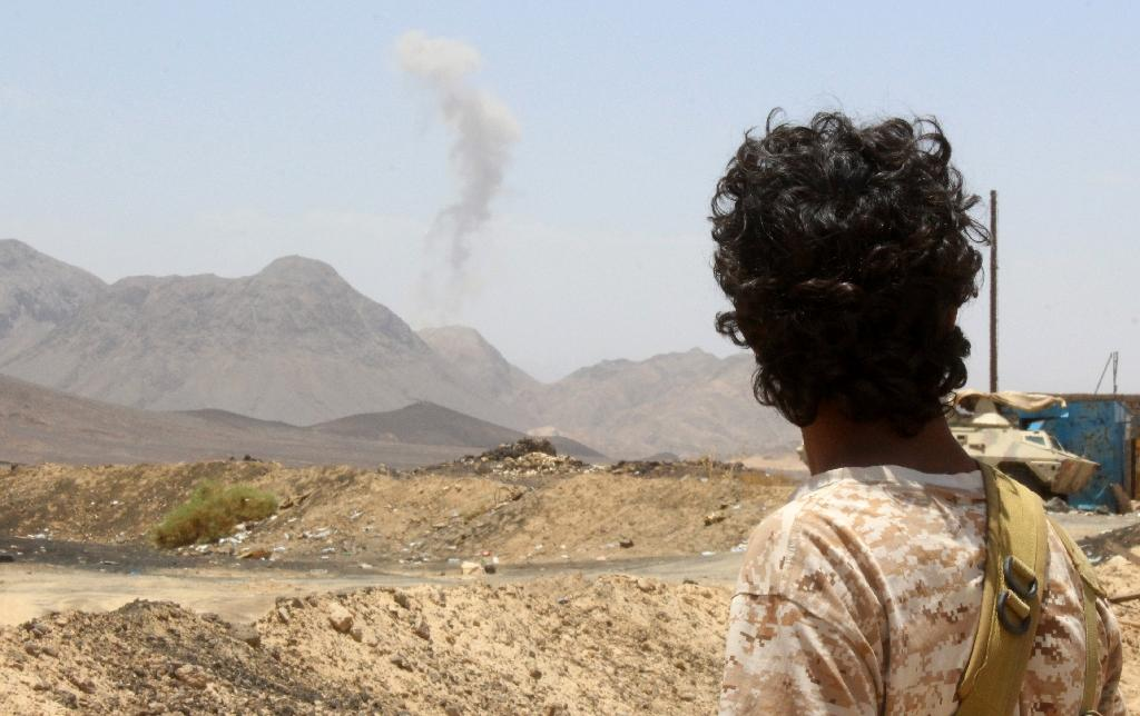 A Yemeni fighter looks at smoke rising in the distance in the Sirwah area, in Marib province on April 10, 2016 (AFP Photo/Nabil Hassan)