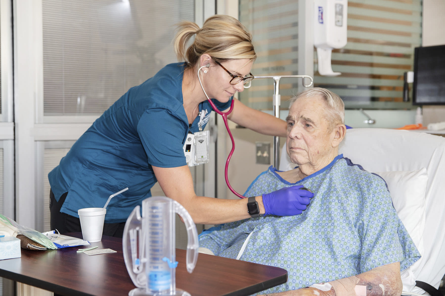 In this July 16, 2019 photo provided by the VA Eastern Colorado Health Care System, George Barrett, 85, of Lakewood, Colo., is checked by nurse Renee Whitley as he recuperates from open-heart surgery at the Rocky Mountain Regional VA Medical Center in Aurora, Colo. The hospital helped the American College of Surgeons test new standards to improve surgical care for older adults. (Shawn Fury/VA Eastern Colorado Health Care System via AP)