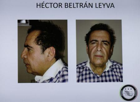 Pictures of head of Beltran Leyva drug cartel Hector Beltran Leyva are seen displayed on a television screen during a news conference at the Attorney General's Office building in Mexico City
