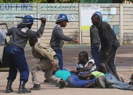 Riot police detain residents of Epworth suburb after a protest by taxi drivers turned violent in Harare