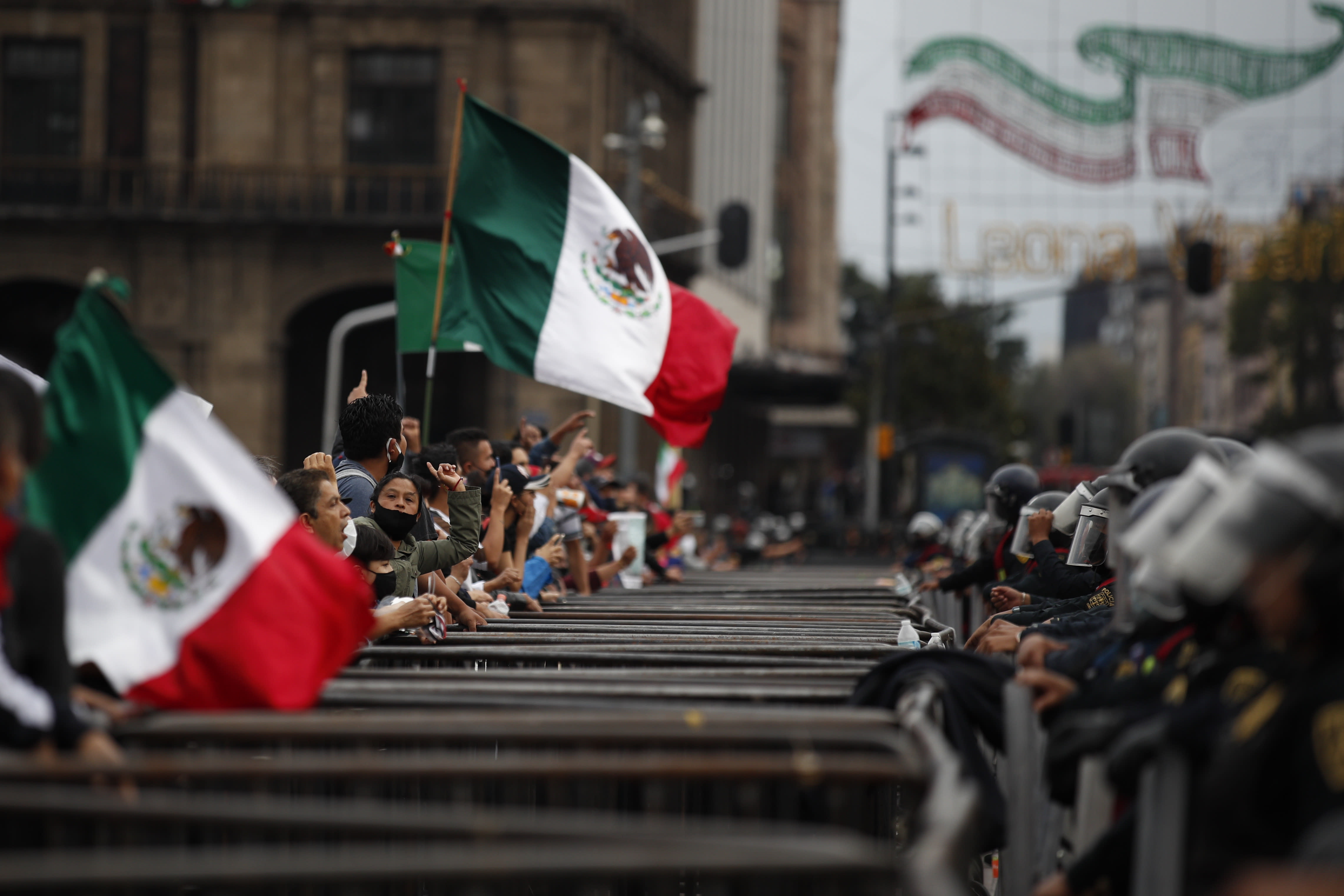 Some participants in a protest marking the sixth anniversary of the forced disappearance of 43 teachers' college students shout over a barricade and a line of police toward unrelated protesters camping out in Mexico City's main square to call for the renunciation of the president, Saturday, Sept. 26, 2020. (AP Photo/Rebecca Blackwell)