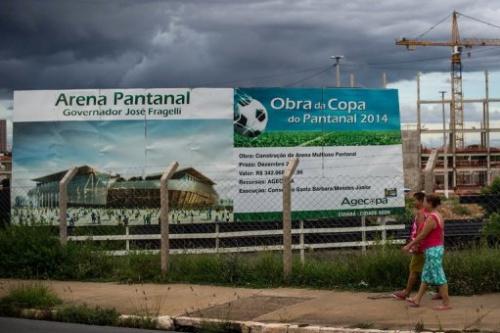 Un grupo de personas pasa ante un cartel en la ciudad brasileña de Cuiabá