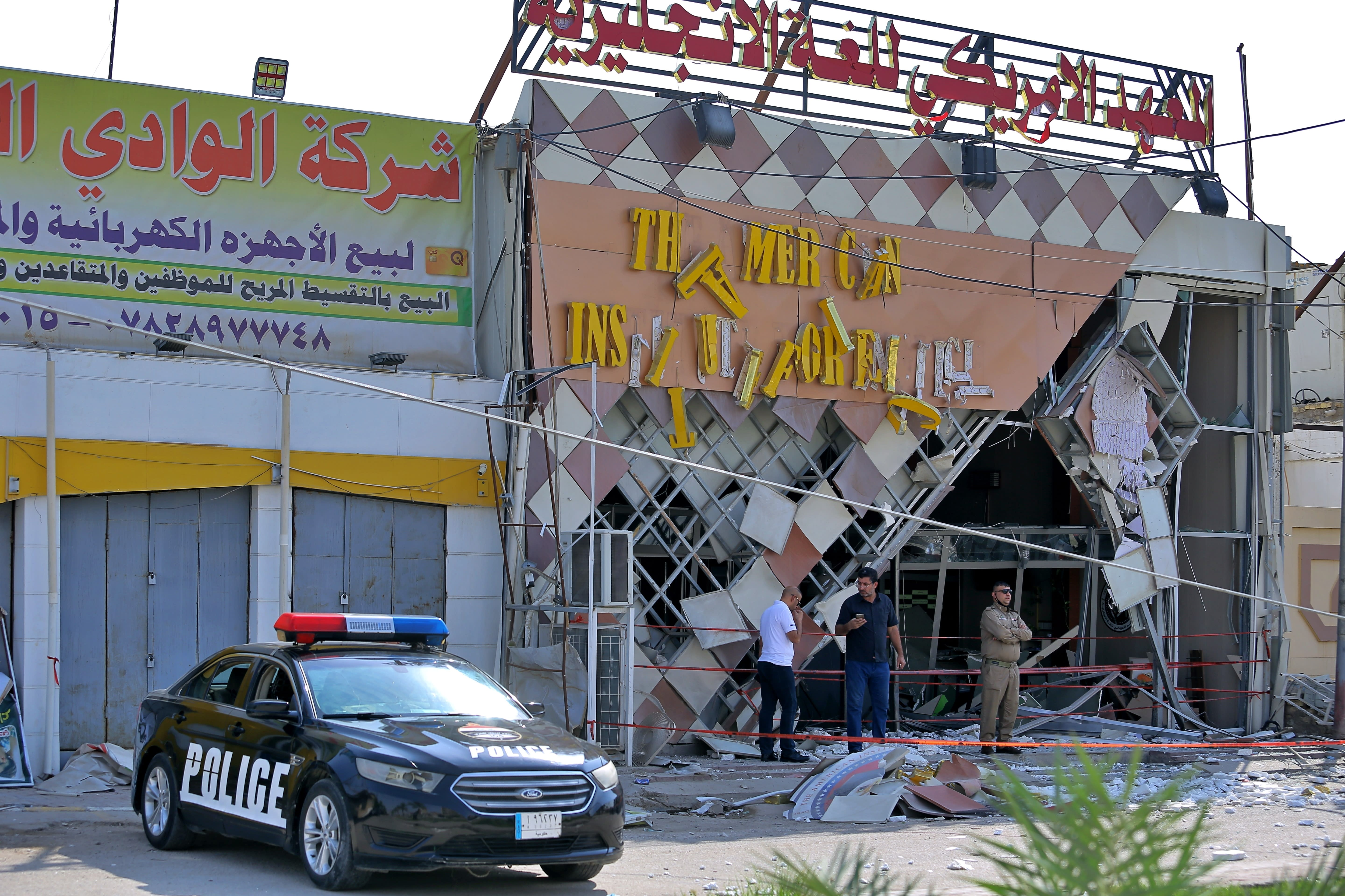 Security forces stand guard near the site of an attack on the American Institute for English Learning in Najaf, Iraq, Friday, Sept. 18, 2020. An IED attack on the American Institute for English Learning in southern Iraq caused major damage without casualties in the early hours on Friday. according to Iraq security officials. (AP Photo/Anmar Khalil)