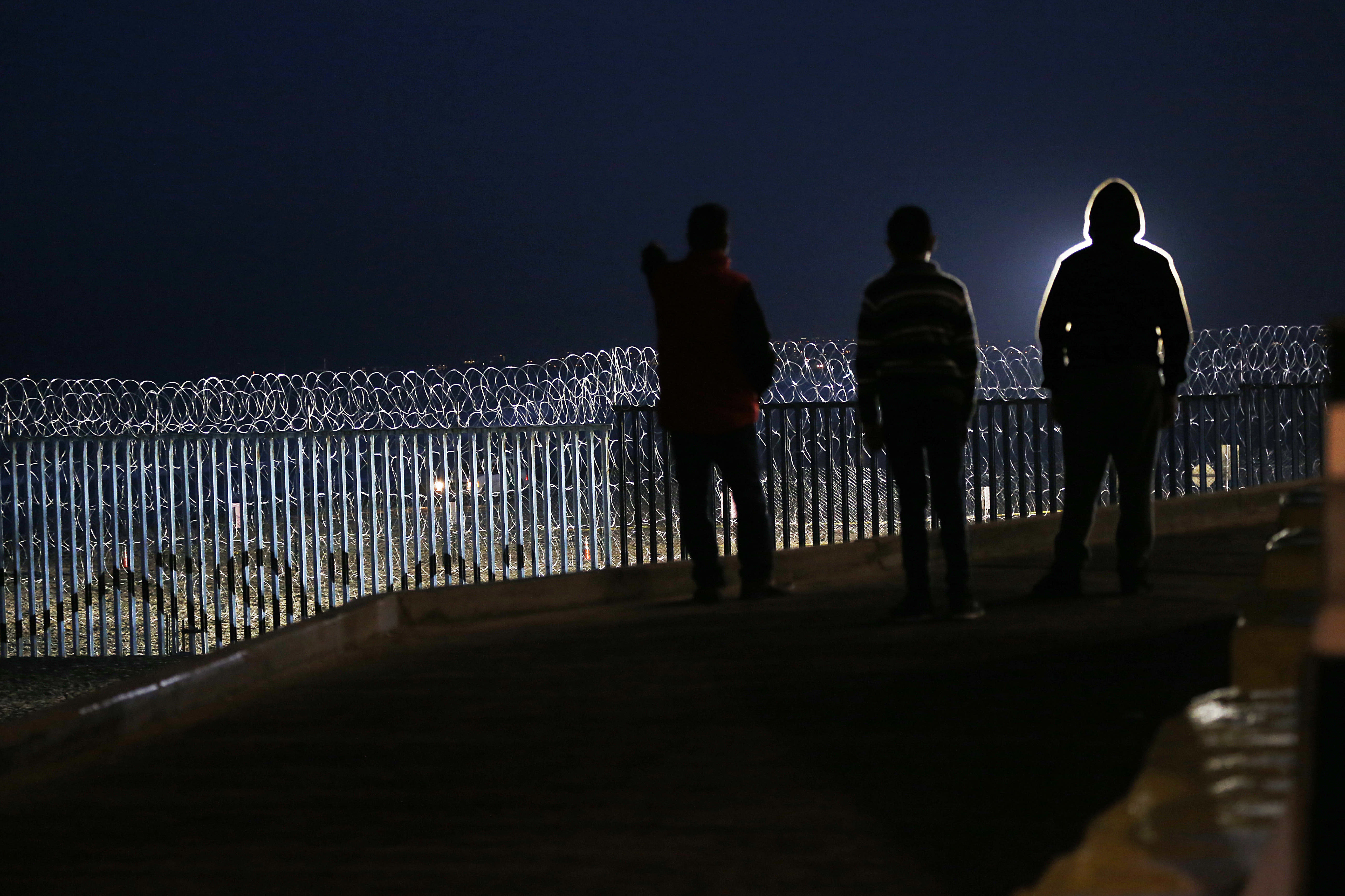 """Residents stand on a hill before barriers, wrapped in concertina wire, separating Mexico and the United States, where the border meets the Pacific Ocean, in Tijuana, Mexico, Saturday, Nov. 17, 2018. Many of the nearly 3,000 migrants have reached the border with California. The mayor has called the migrants' arrival an """"avalanche"""" that the city is ill-prepared to handle. (AP Photo/Marco Ugarte)"""