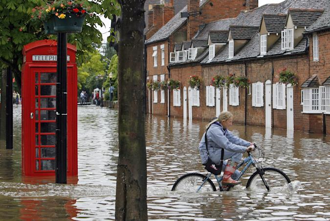 A woman rides a bicycle through a foot of water next to an iconic British red telephone box.