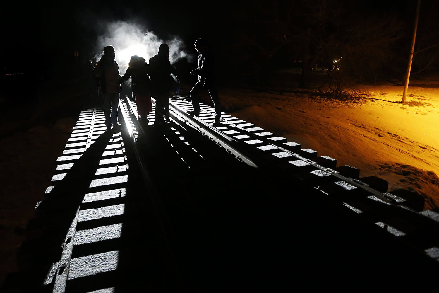 <p>Migrants from Somalia cross into Canada from the United States by walking down a train track early Sunday, Feb. 26, 2017, into the town of Emerson, Manitoba, where they will seek asylum at the Canada Border Services Agency. (Photo: John Woods/The Canadian Press via AP) </p>