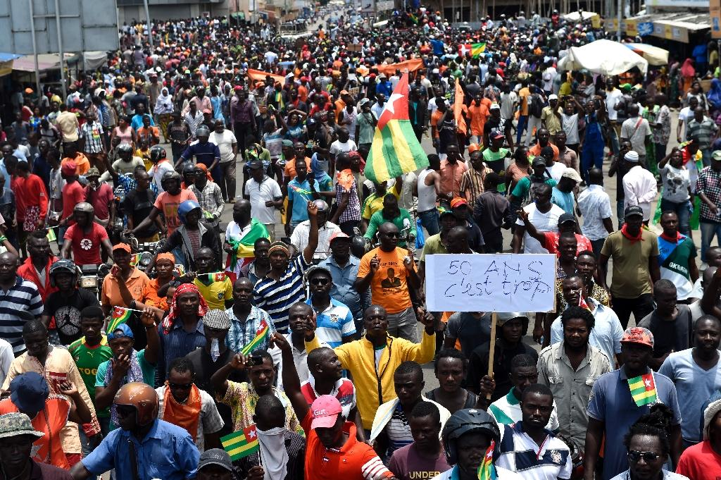 Protesters carry flags and placards while they march shouting slogans as they call for reforms during an anti-government rally in Lome on September 6, 2017