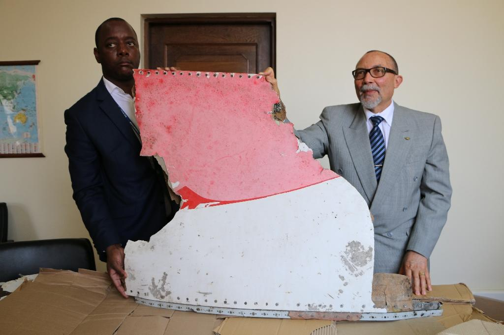 Joao de Abreu (right), President of Mozambique's Civil Aviation Institute (IACM), and a marshal display pieces of suspected aircraft wreckage found off the east African coast of Mozambique, in Maputo on September 5, 2016