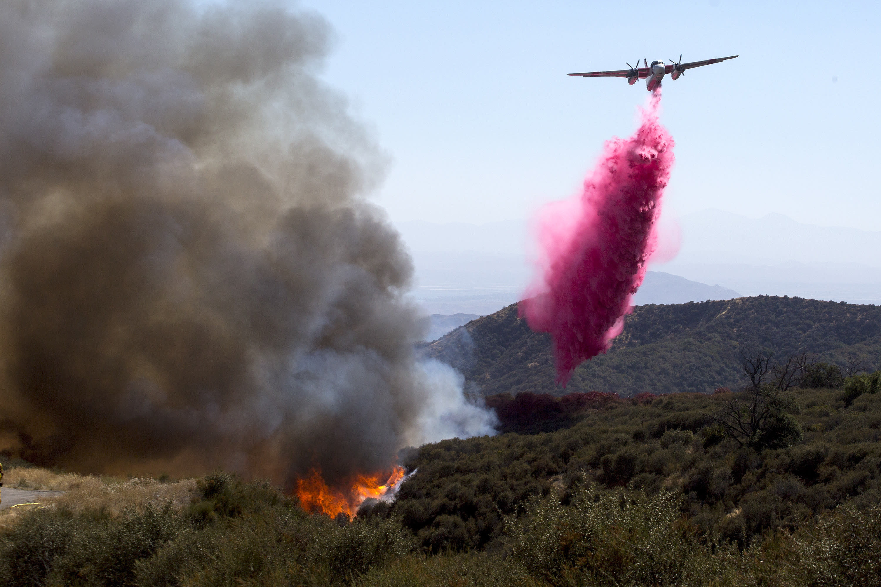 An air tanker drops fire retardant at the Apple Fire in Cherry Valley, Calif., Saturday, Aug. 1, 2020. A wildfire northwest of Palm Springs flared up Saturday afternoon, prompting authorities to issue new evacuation orders as firefighters fought the blaze in triple-degree heat. (AP Photo/Ringo H.W. Chiu)