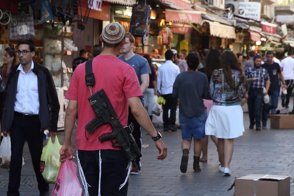 Israelis carry their personal rifles at Jerusalem's Mahne Yehuda market on October 9, 2015 (AFP Photo/Gali Tibbon)
