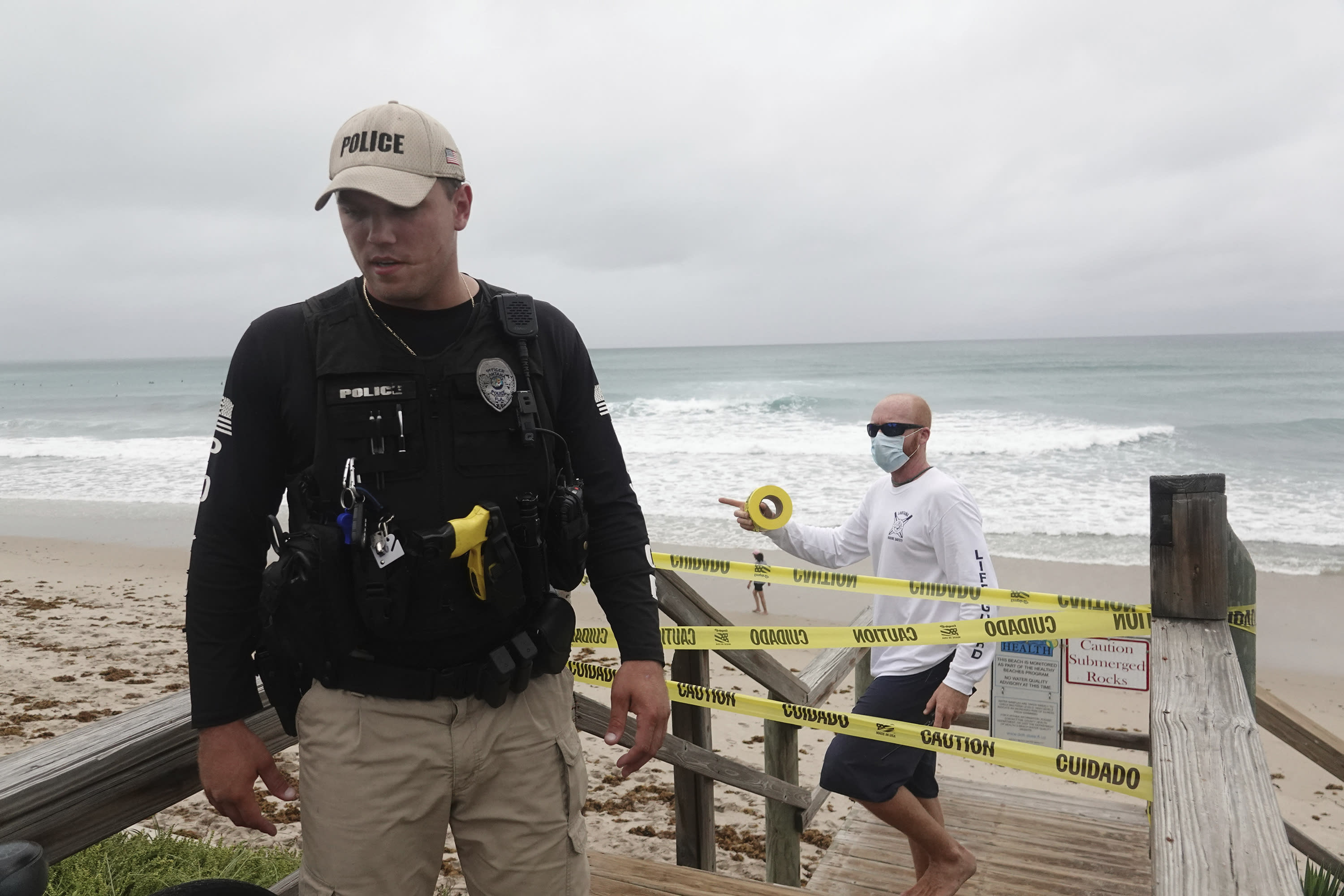 Police and lifeguards from the Town of Lantana close the beach and boardwalk, Sunday, Aug. 2, 2020, as Tropical Storm Isaias brushes past the East Coast of Florida. (Joe Cavaretta/South Florida Sun-Sentinel via AP)