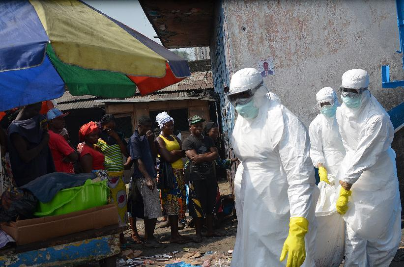 Red Cross workers wearing protective suits carry the body of a victim of Ebola during a burial in Monrovia, on January 5, 2015 (AFP Photo/Zoom Dosso)