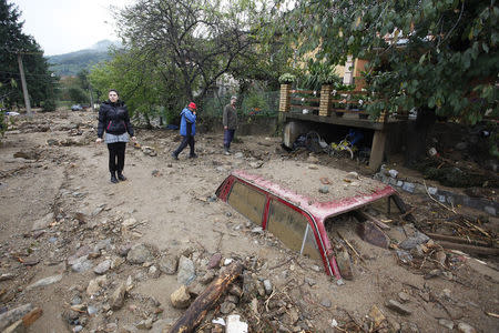 People pass by a vehicle almost completely submerged on a street covered with mud due to heavy floods in Tekija village e