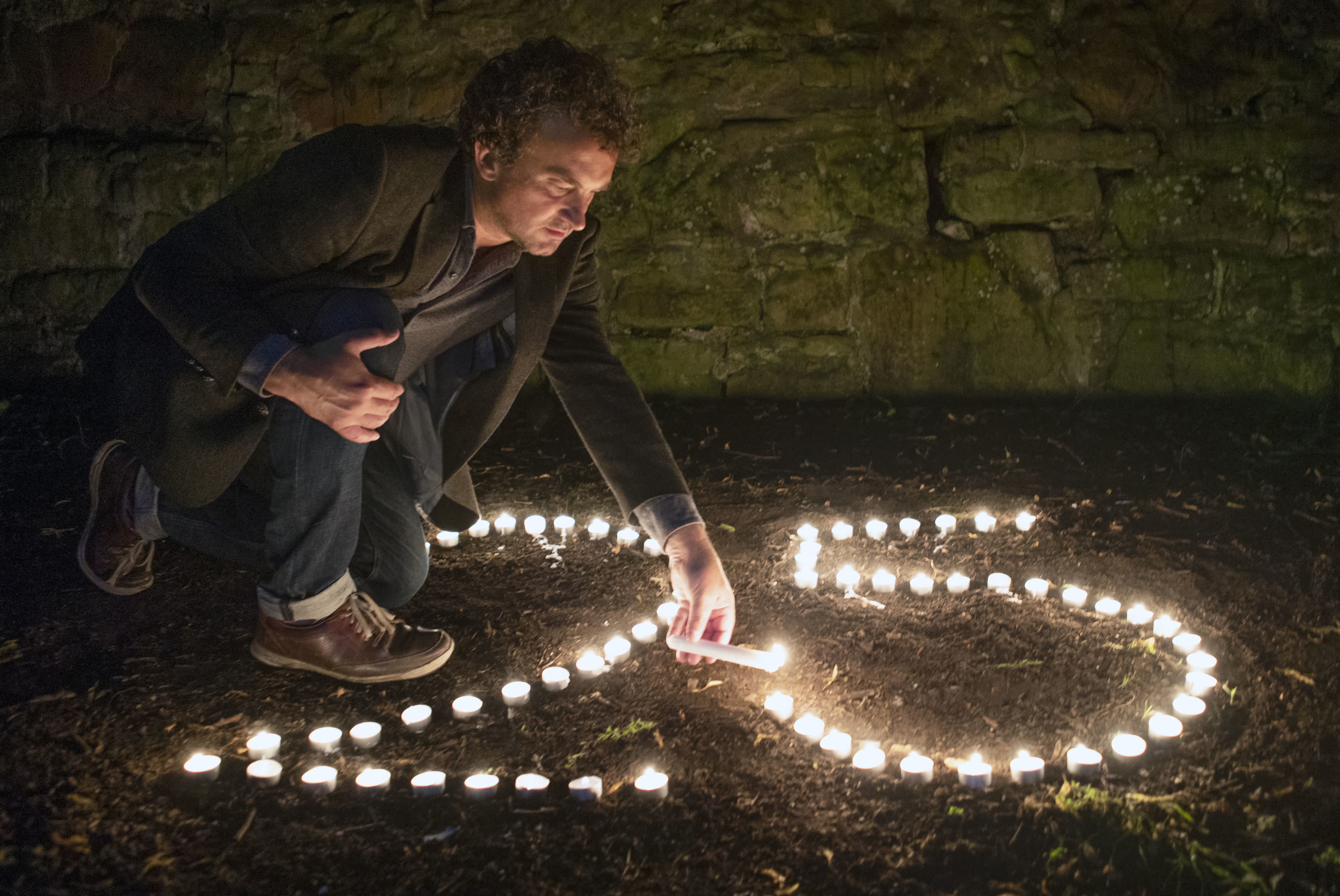 BAFTA award-winning film director Samir Mehanovic, who came to the UK as an immigrant from the Bosnian war in 1995 and now lives in Scotland, lights candles to commemorate the 25th anniversary of the Srebrenica genocide, in Edinburgh, Scotland, Thursday July 9, 2020. In July 1995, Bosnian Serb forces massacred over 8,000 men and boys, an event that is officially marked on Saturday July 10, 2020. (Jane Barlow/PA via AP)