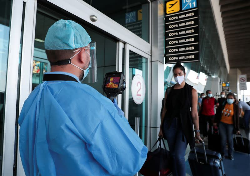 A healthcare worker measures the temperatures of travelers before entering the Tocumen International Airport during the coronavirus disease (COVID-19) outbreak, in Panama City