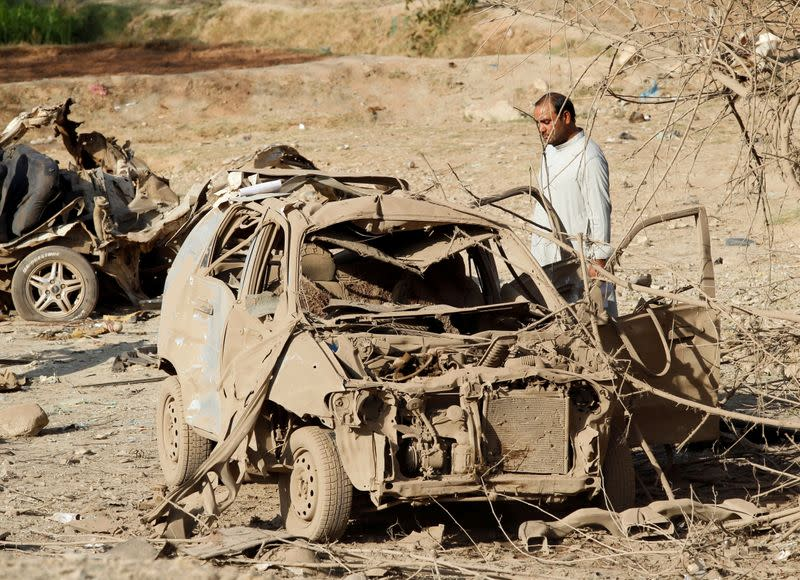 FILE PHOTO: An Afghan man inspects the wreckage of a car at the site of a truck bomb blast in Ghani Khel district of Nangarhar province