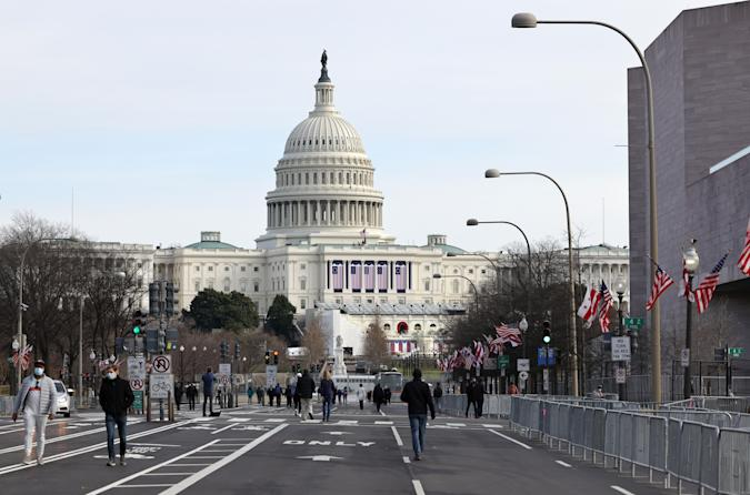 WASHINGTON, DC - JANUARY 16: Pedestrians walk along Pennsylvania Avenue near the U.S. Capitol on January 16, 2021 in Washington, DC. After last week's riots at the U.S. Capitol Building, the FBI has warned of additional threats in the nation's capital and in all 50 states. According to reports, as many as 25,000 National Guard soldiers will be guarding the city as preparations are made for the inauguration of Joe Biden as the 46th U.S. President. (Photo by Michael M. Santiago/Getty Images)