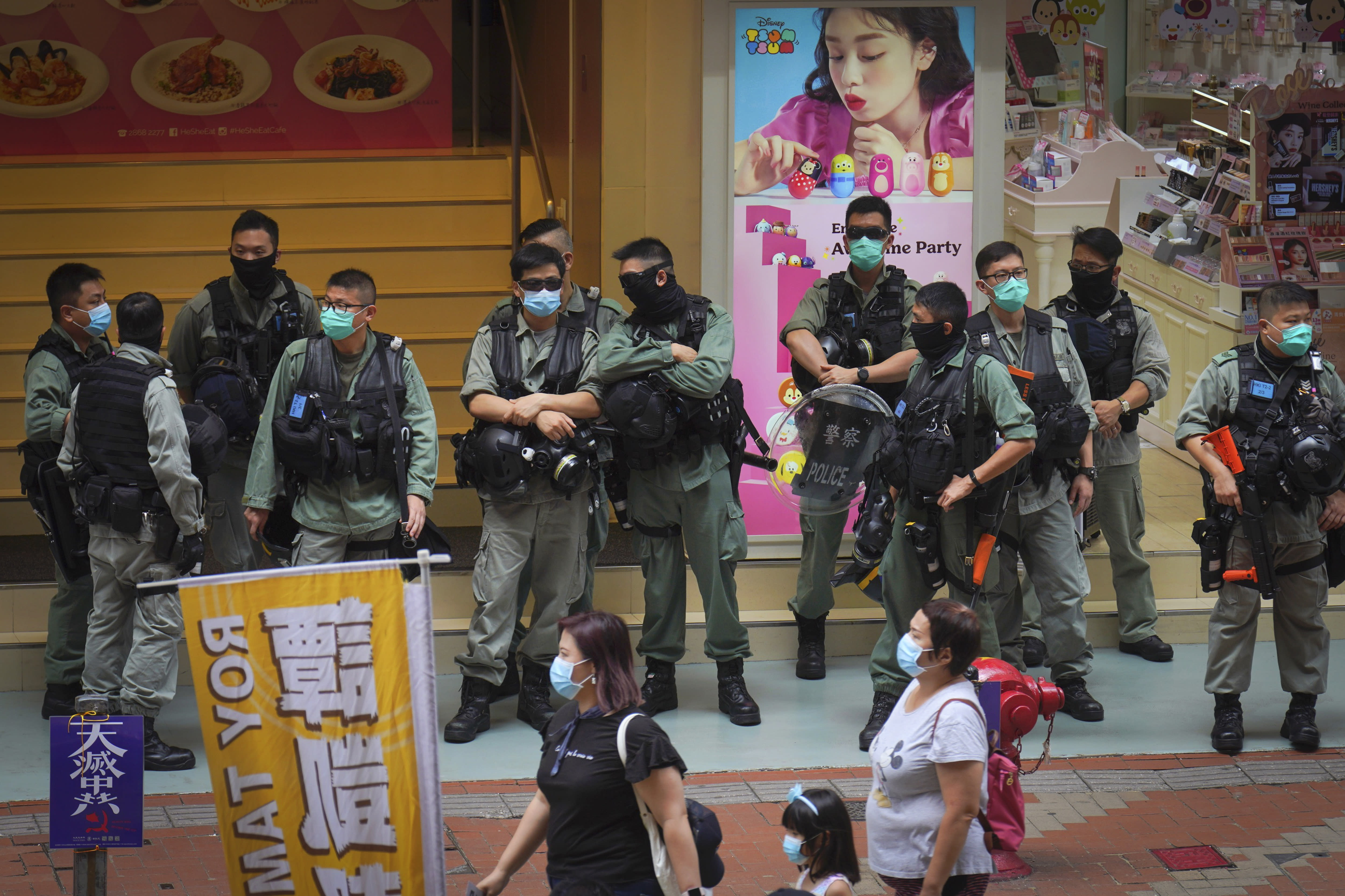 Police stand guard in Causeway Bay before the annual handover march in Hong Kong, Wednesday, July. 1, 2020. Hong Kong marked the 23rd anniversary of its handover to China in 1997, and just one day after China enacted a national security law that cracks down on protests in the territory. (AP Photo/Vincent Yu)