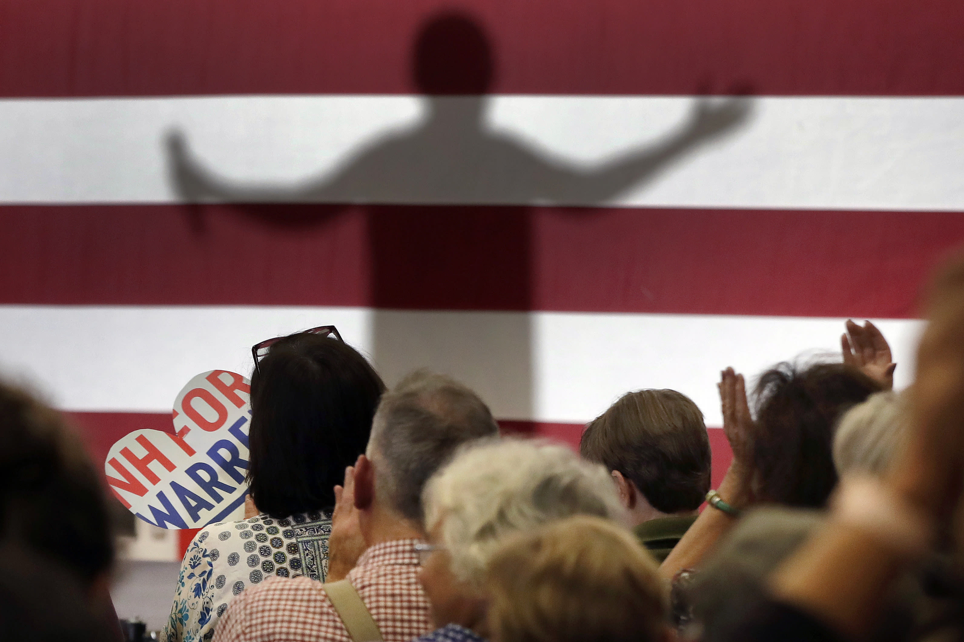 """FILE - In this Tuesday, Oct. 29, 2019 file photo, a shadow of Democratic presidential candidate Sen. Elizabeth Warren, D-Mass., is cast on a U.S. flag backdrop as supporters applaud during a campaign event in Laconia, N.H. On Friday, Jan. 17, 2020, The Associated Press reported on stories circulating online incorrectly asserting that the Warren presidential campaign staged or digitally altered a text message exchange of a Bernie Sanders campaign volunteer calling Warren """"Pocahontas."""" The Sanders campaign told the AP a rogue volunteer enrolled in their system, sending out the text message. The cell phone number listed on the text message has been disconnected. (AP Photo/Elise Amendola)"""