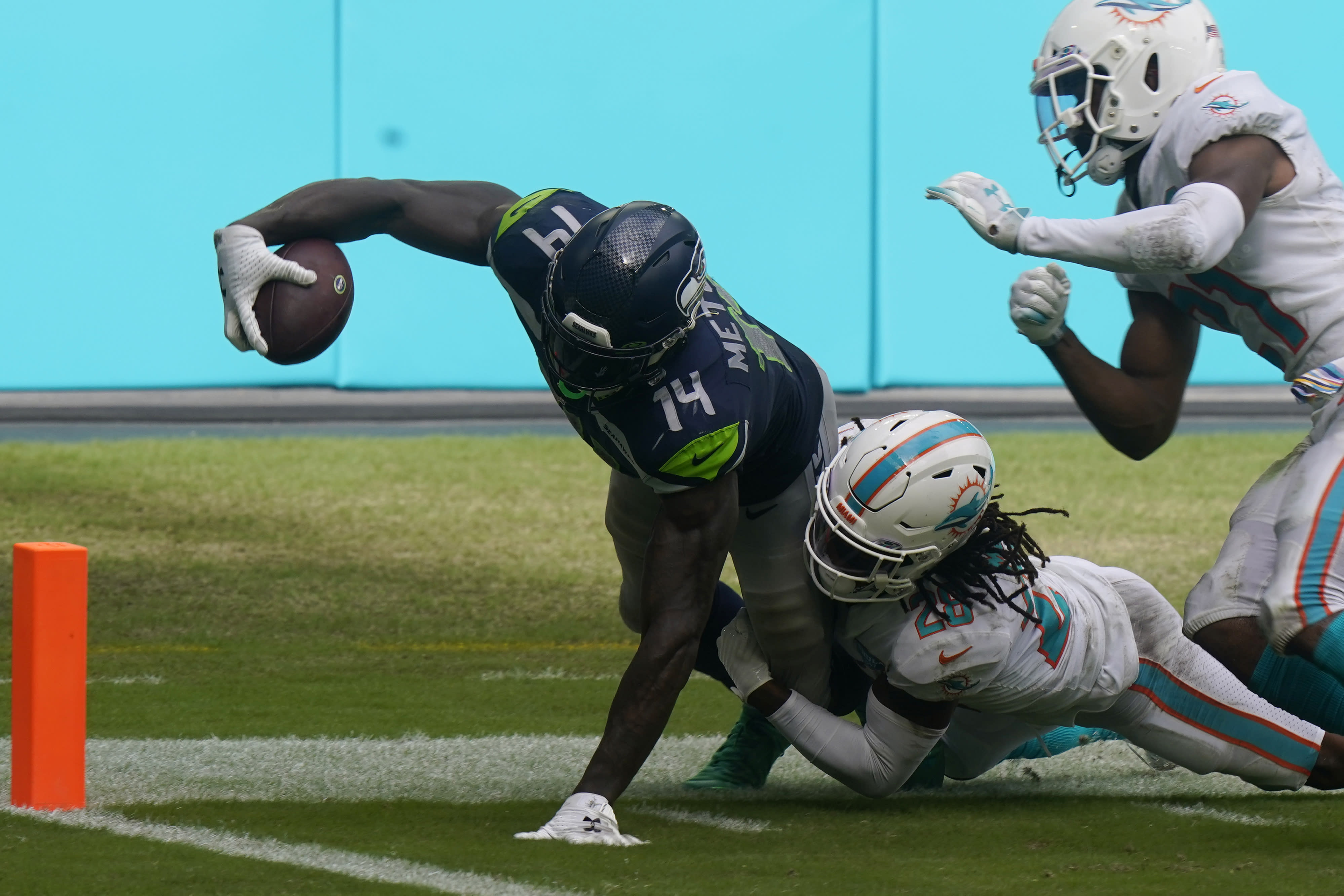Miami Dolphins strong safety Bobby McCain (28) takes Seattle Seahawks wide receiver DK Metcalf (14) near the end zone, during the second half of an NFL football game, Sunday, Oct. 4, 2020, in Miami Gardens, Fla. (AP Photo/Lynne Sladky)