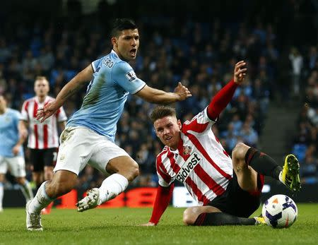 Manchester City's Aguero challenges Sunderland's Wickham during their English Premier League soccer match at the Etihad stadium in Manchester