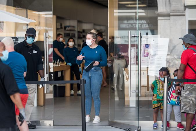 CHARLESTON, SC - MAY 13: An employee at the Apple Store helps a customer on May 13, 2020 in Charleston, South Carolina. Customers had their temperatures taken and were required to wear masks at the South Carolina store, as locations in Idaho, Alabama, and Alaska reopened as well following forced closures due to the coronavirus. (Photo by Sean Rayford/Getty Images)