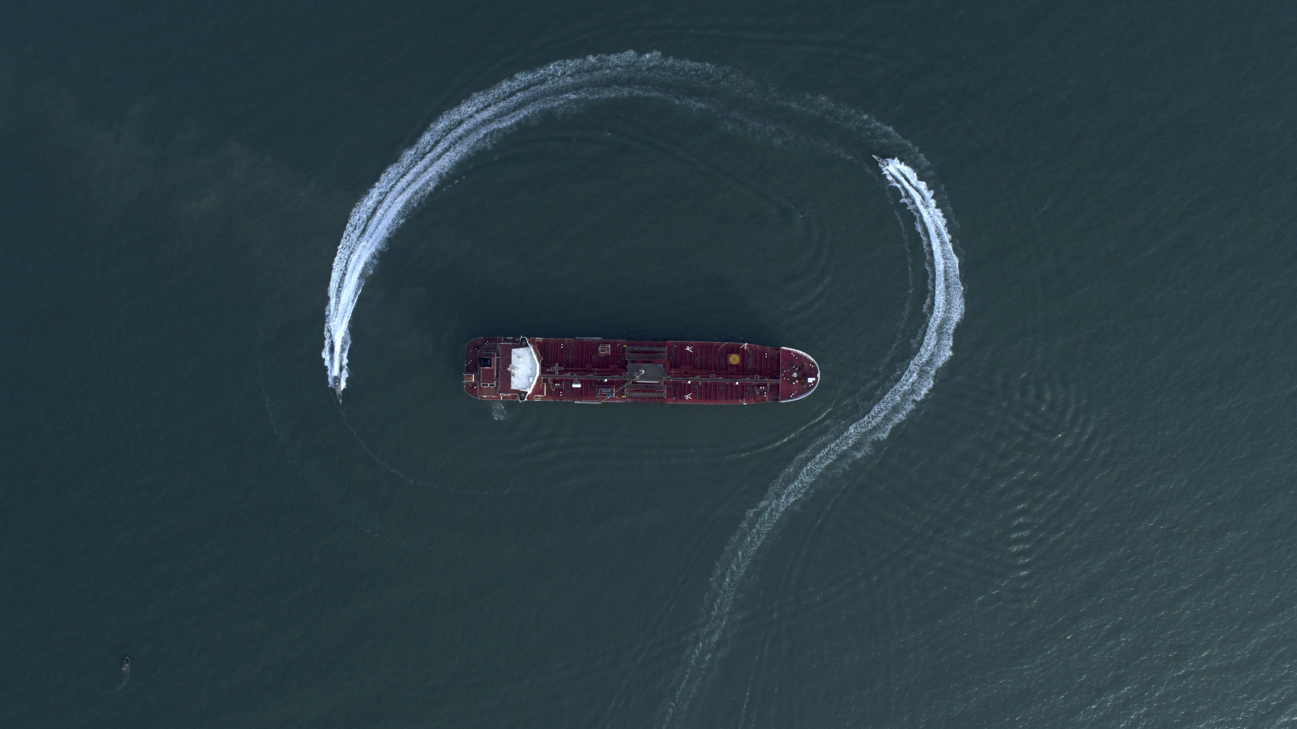 FILE - In this July 21, 2019 file photo, an aerial view shows a speedboat of Iran's Revolutionary Guard moving around the British-flagged oil tanker Stena Impero, which was seized in the Strait of Hormuz by the Guard, in the Iranian port of Bandar Abbas. The U.S. Navy is trying to put together a new coalition of nations to counter what it sees as a renewed maritime threat from Iran. Meanwhile, Iran finds itself backed into a corner and ready for a possible conflict. It stands poised on Friday, Sept. 6, 2019, to further break the terms of its 2015 nuclear deal with world powers. (Morteza Akhoondi/Tasnim News Agency via AP, File)