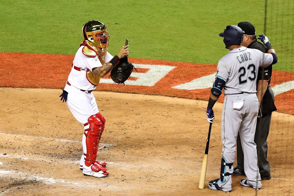 adier Molina #4 of the St. Louis Cardinals and the National League takes a photograph of Nelson Cruz #23 of the Seattle Mariners and the American League and umpire Joe West in the sixth inning during the 88th MLB All-Star Game at Marlins Park on July 11, 2017 in Miami, Florida.