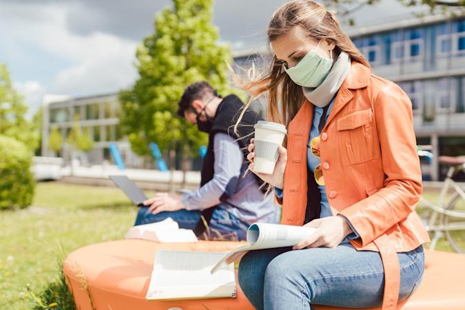 Woman student on college campus learning wearing face mask while working on her laptop