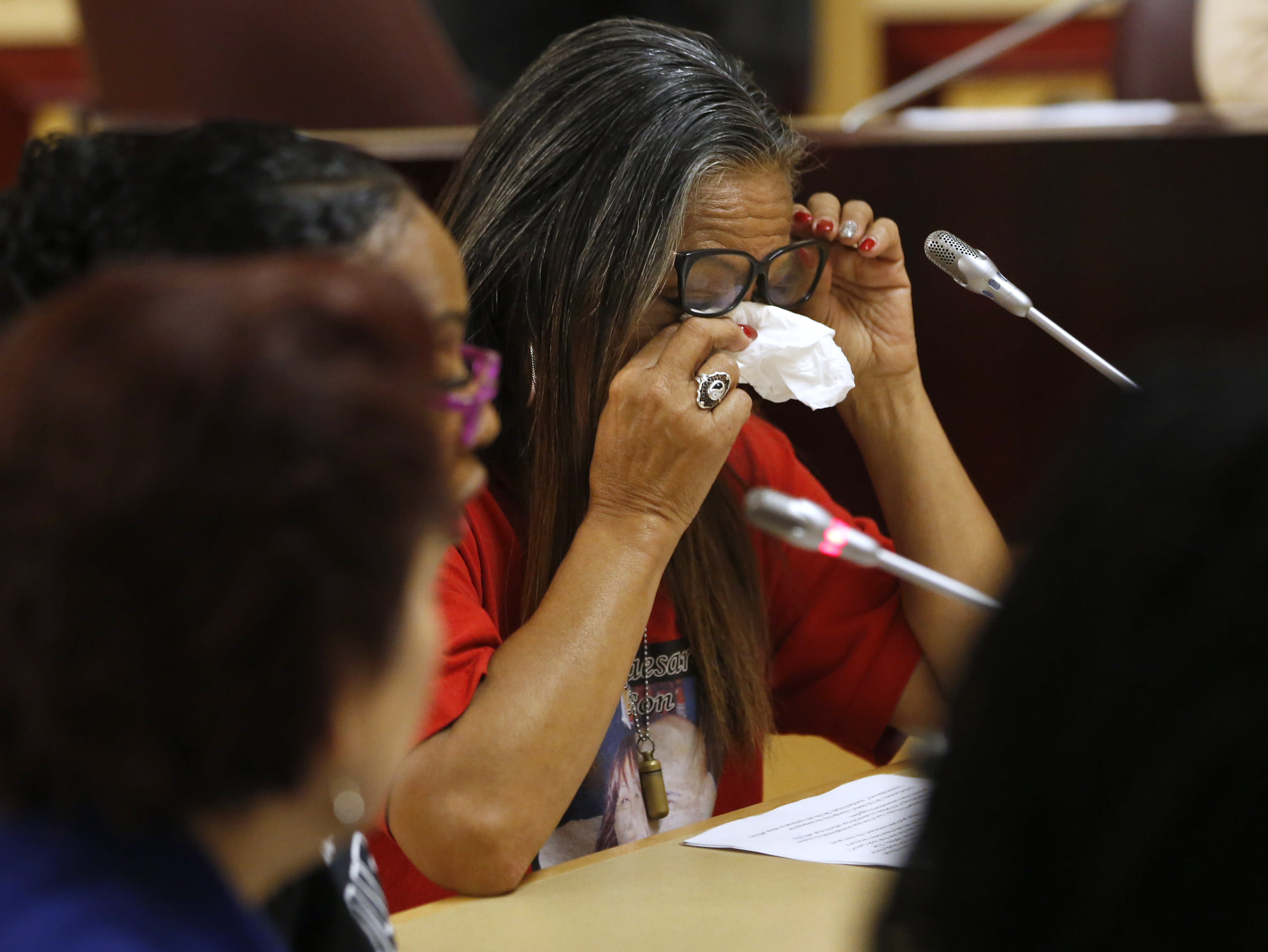 Theresa Smith, right, the mother of Caesar Cruz, who was killed in a confrontation with police, wipes her eyes after testifying against a police-backed law enforcement training bill by state Sen. Anna Caballero, D-Salinas, during a hearing at the Capitol Tuesday, April 23, 2019, in Sacramento, Calif. Lawmakers worked to find common ground between law enforcement organizations, which support Caballero's bill and reformers supporting a competing measure, by Democratic Assemblywoman Shirley Weber, that would adopt the first-in-the-nation standards designed to limit fatal shootings by police. (AP Photo/Rich Pedroncelli)