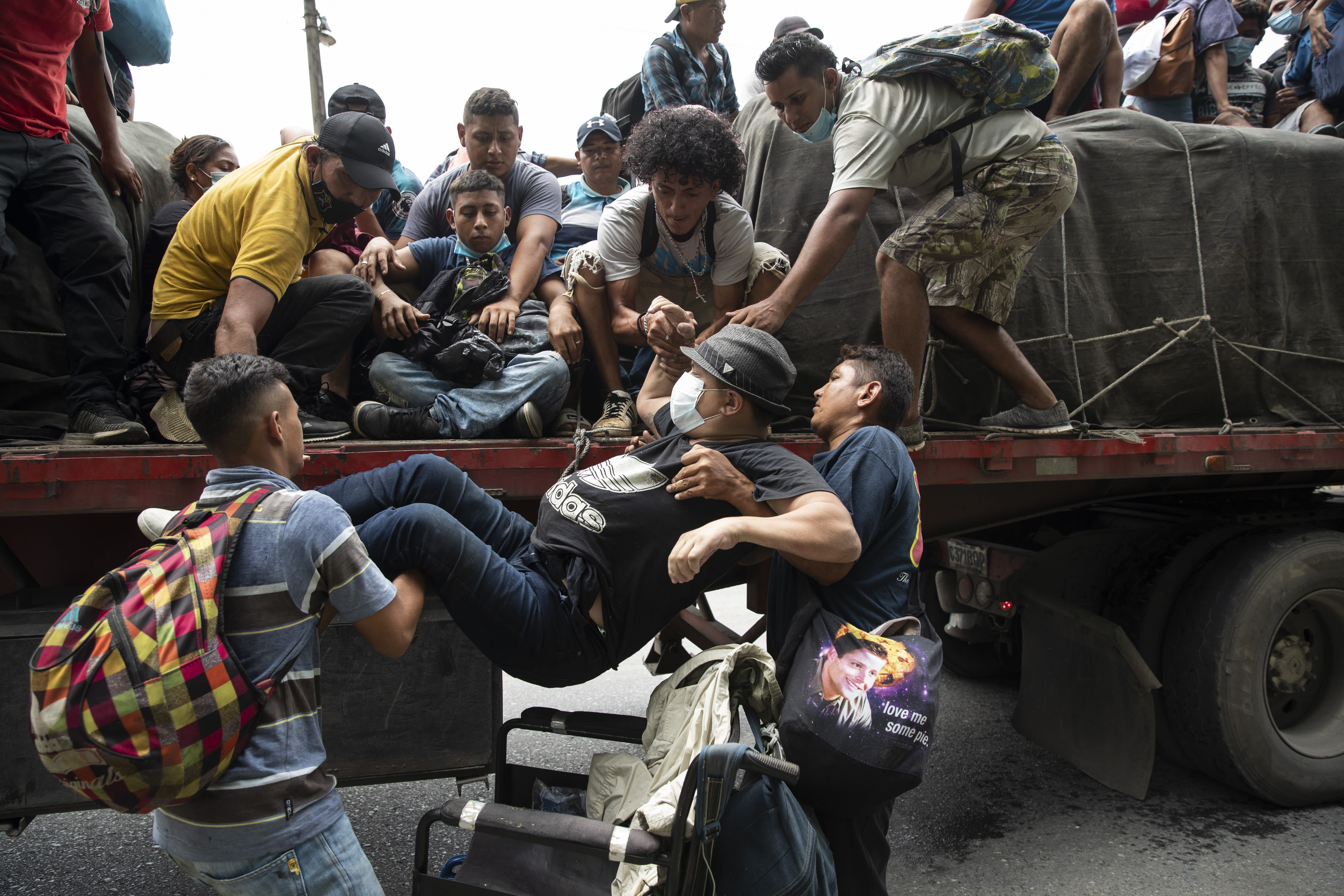 Wheelchair bound migrant Wilmer Chavez, 33, is helped by fellow migrants on to the back of a freight truck that stopped to give the migrants a free ride in Rio Dulce, Guatemala, Friday, Oct. 2, 2020. A new caravan of about 2,000 migrants set out from neighboring Honduras in hopes of reaching the United States. (AP Photo/Moises Castillo)