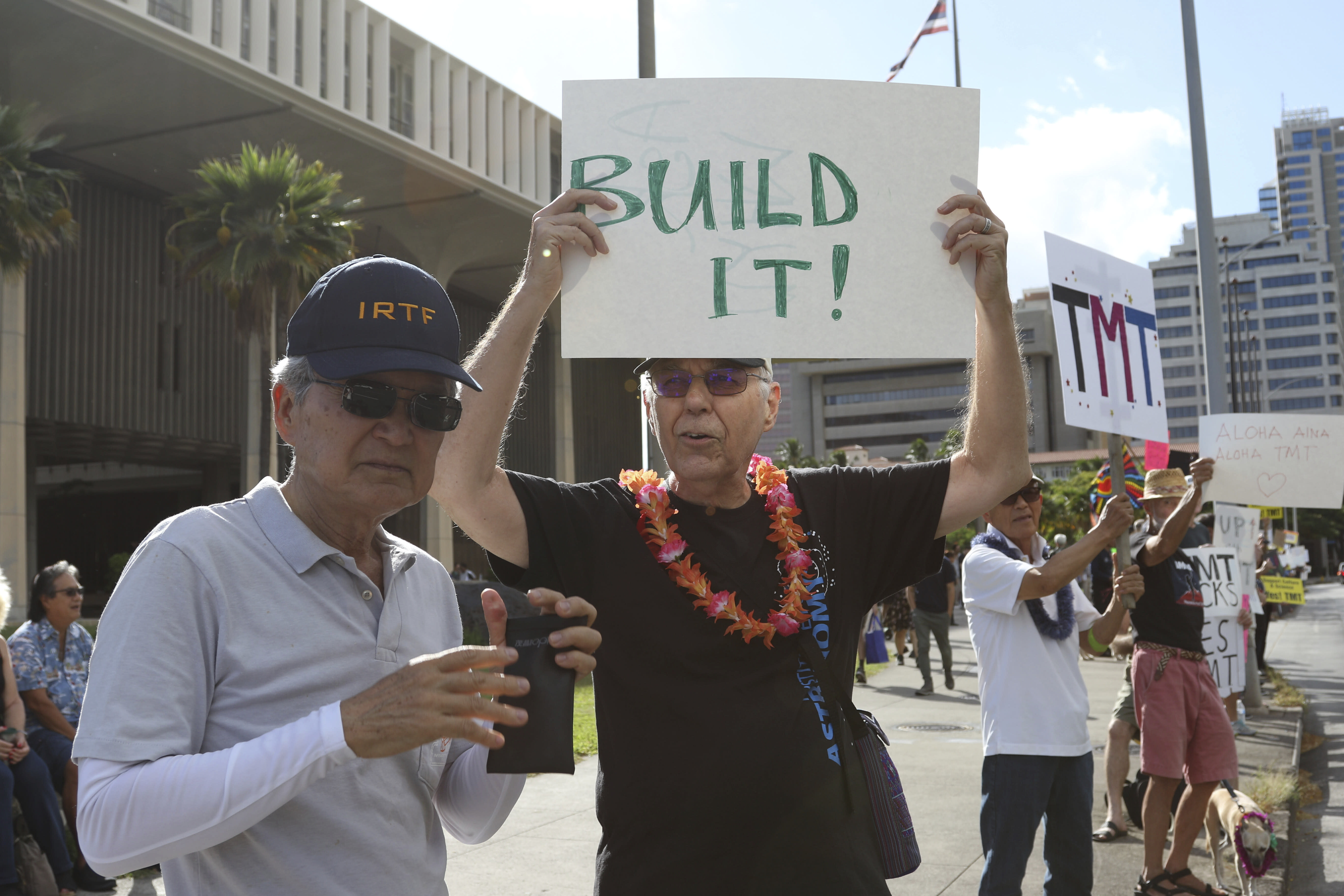 """Astronomers Alan Stockton, center, holding a sign saying """"Built It!,"""" and Alan Tokunaga, left, join a rally in support the Thirty Meter Telescope outside the Hawaii State Capitol in Honolulu on Thursday, July 25, 2019. Supporters said the giant telescope planned for Hawaii's tallest mountain will enhance humanity's knowledge of the universe and bring quality, high-paying jobs, as protesters blocked construction for a second week. (AP Photo/Audrey McAvoy)"""