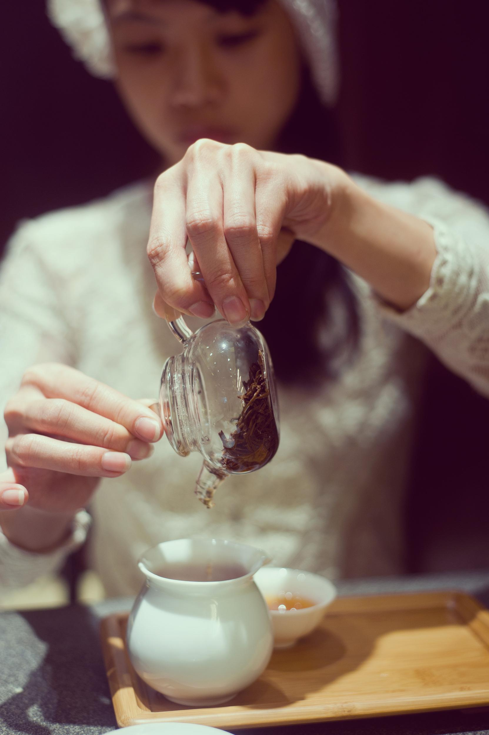 Close up of human hands of woman pouring tea