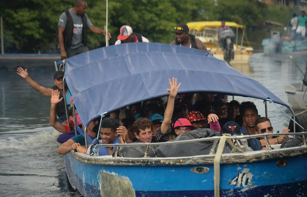 Cuban and Haitians migrants get into a boat to be taken from Colombia to illegally cross to Panama through the jungle, on August 6, 2016