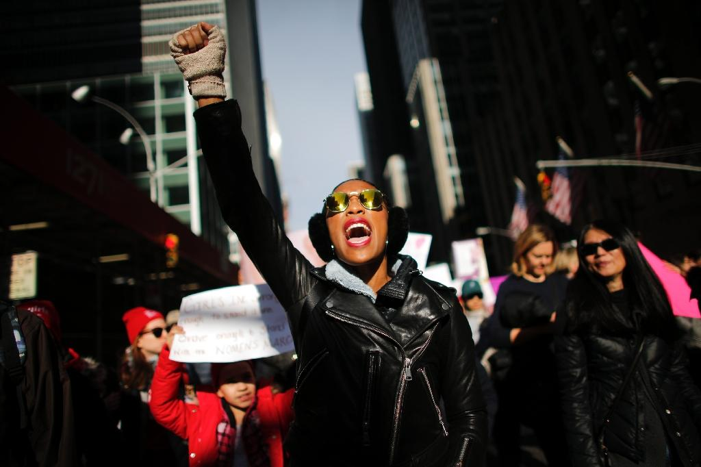 A woman protests in New York City where hundreds of thousands marched in protest of Donald Trump, one year after his inauguration (AFP Photo/KENA BETANCUR)