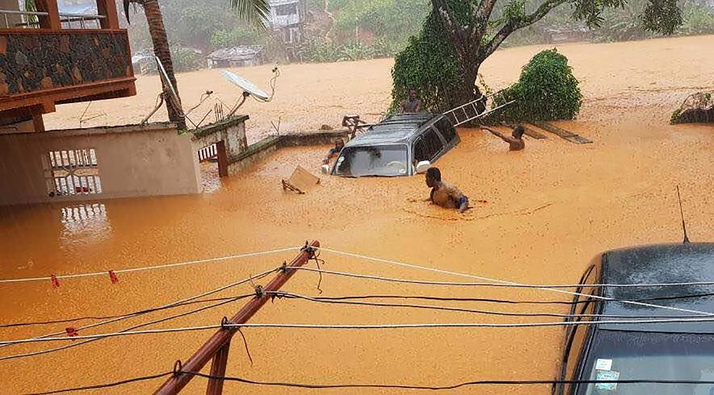 Residents struggled to traverse roads that were turned into churning rivers of mud after Sierra Leone's capital of Freetown was struck by heavy rains (AFP Photo/STR)