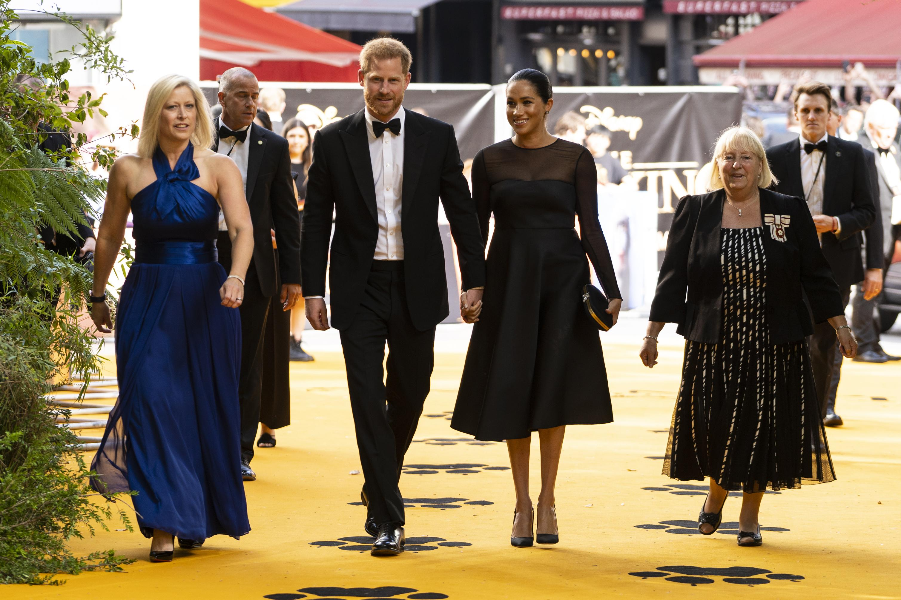The duchess wore a black dress and heels with her hair swept up.