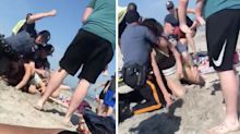 Policeman filmed punching woman in head during beach arrest
