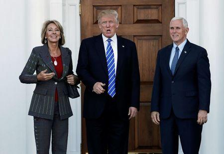 U.S. President-elect Donald Trump (C) and Vice President-elect Mike Pence stand with Betsy DeVos (L) before their meeting at the main clubhouse at Trump National Golf Club in Bedminster, New Jersey, U.S., November 19, 2016. REUTERS/Mike Segar/File Photo