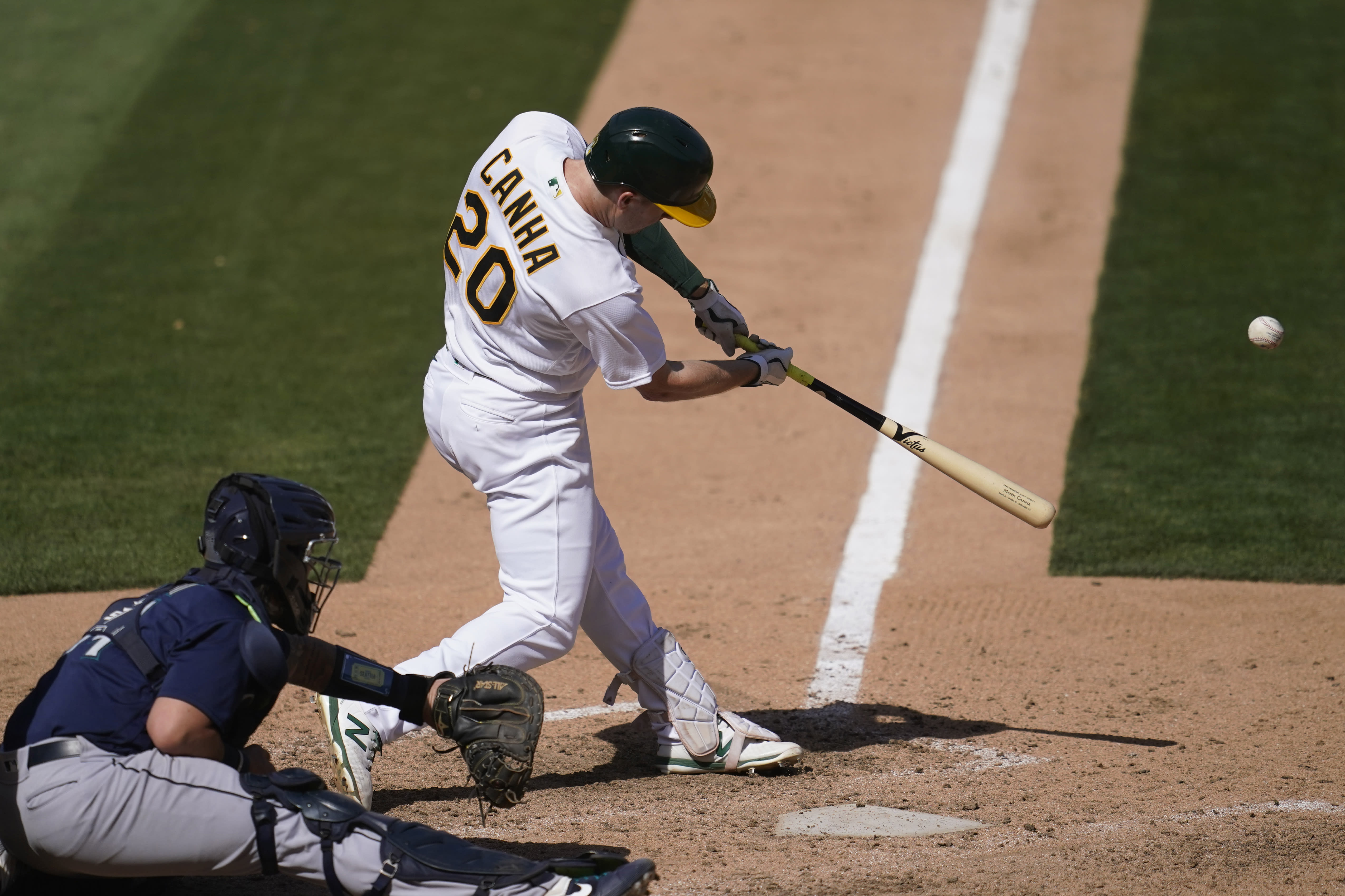 Oakland Athletics' Mark Canha (20) hits a two-run double in front of Seattle Mariners catcher Joseph Odom during the seventh inning of a baseball game in Oakland, Calif., Sunday, Sept. 27, 2020. (AP Photo/Jeff Chiu)