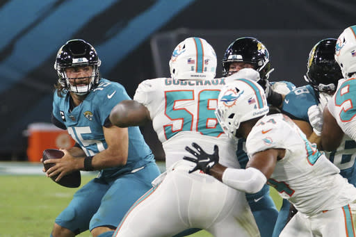 Miami Dolphins defensive tackle Davon Godchaux (56) pressures Jacksonville Jaguars quarterback Gardner Minshew, left, as he looks for a receiver during the first half of an NFL football game, Thursday, Sept. 24, 2020, in Jacksonville, Fla. (AP Photo/Stephen B. Morton)