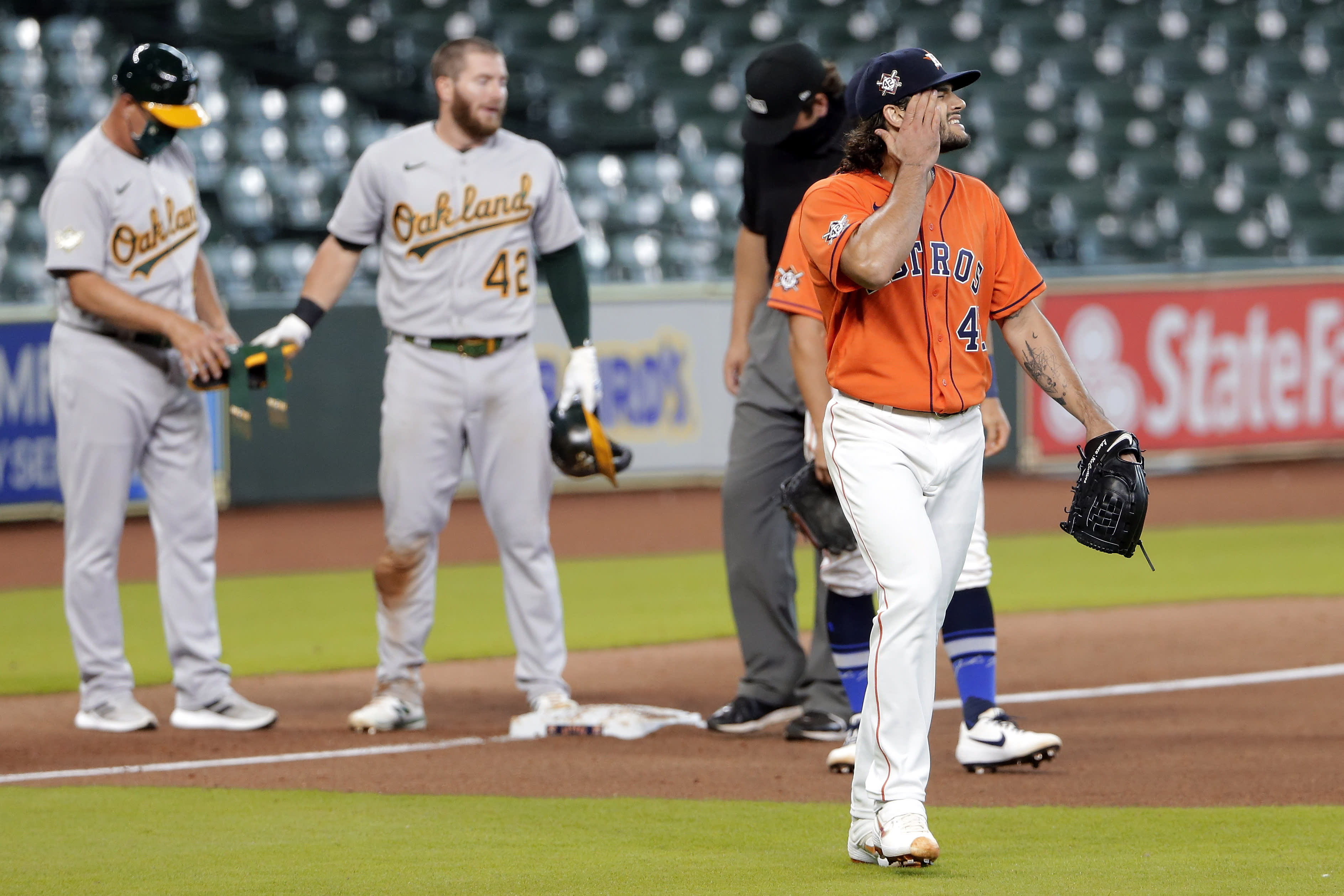 Oakland Athletics' Robbie Grossman stands on third base as Houston Astros starting pitcher Lance McCullers Jr., right, walks by after McCullers' throwing error to first base allowed a triple by him during the sixth inning of the first baseball game of a doubleheader Saturday, Aug. 29, 2020, in Houston. (AP Photo/Michael Wyke)