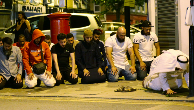 Locals observe prayers at the scene of the attack (PA)