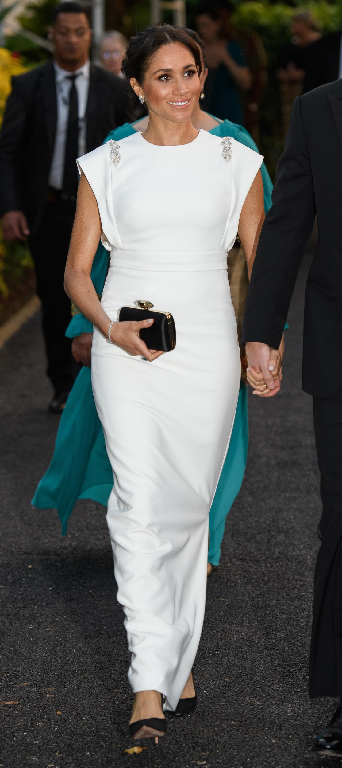 """Meghan looked glamorous as ever ina sleek white gown by Irish designer<a href=""""https://www.shopstyle.com/browse/womens-clothes/theia?gclid=EAIaIQobChMImNGghuSh3gIVBVSGCh36_wFPEAAYASAAEgJ75fD_BwE&jap=1t1&jcpid=8a8ae4cd474ef76201476633c72107bc&jkId=gcp:se_34900:t_kwd-2842879895:ag_9846743997:cp_172830237:n_g:d_c:cr_58408612677:fi_&js=1&jsid=34900&jt=1&t=new&utm_campaign=Theia+-+Alpha&utm_content=58408612677&utm_id=t_kwd-2842879895:ag_9846743997:cp_172830237:n_g:d_c:fi_&utm_medium=PPC&utm_source=Adwords&utm_term=theia"""" target=""""_blank"""">Theia</a>to attend a black-tie reception with the King and Queen of Tonga."""