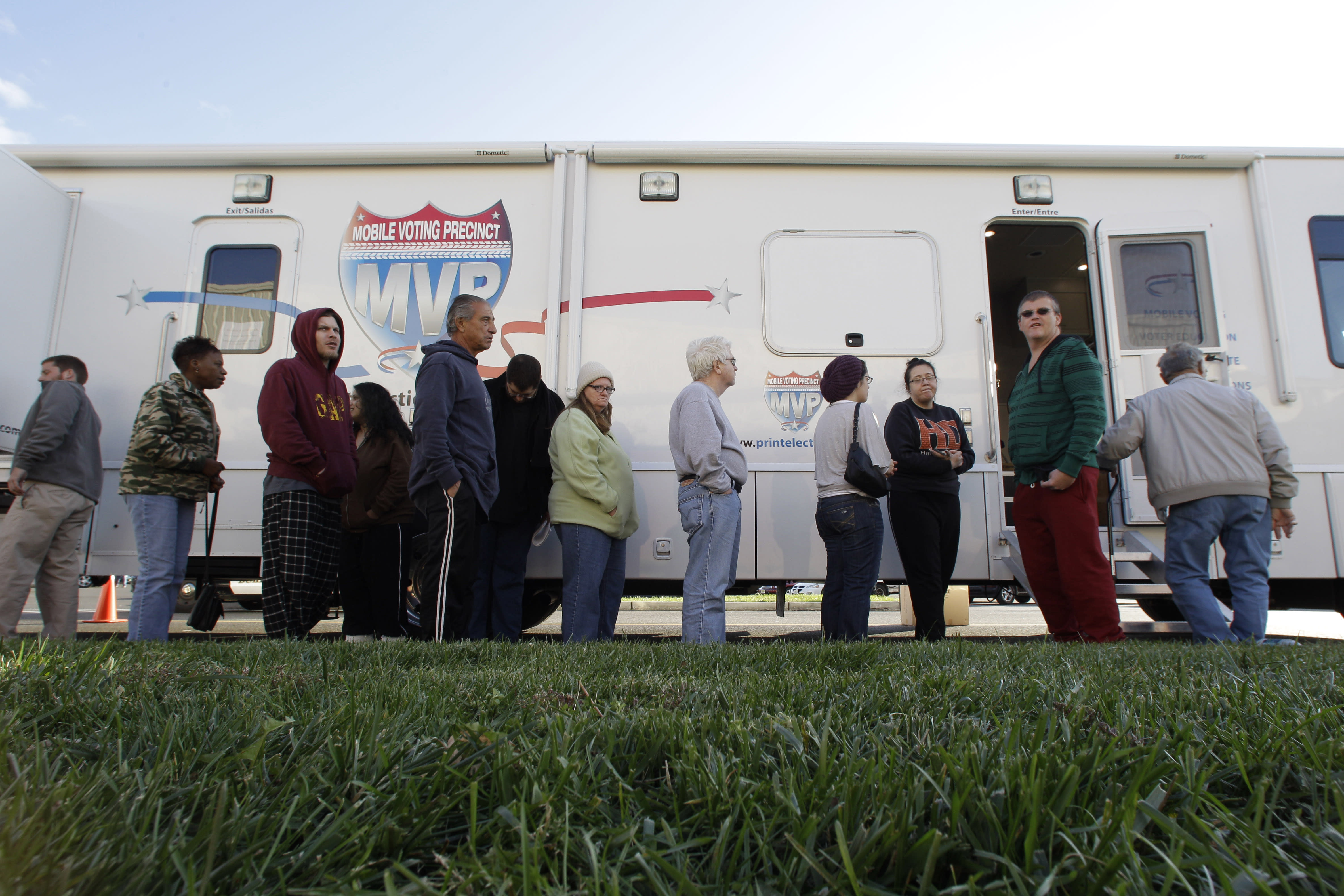 People, many displaced by Superstorm Sandy, line up to vote Monday, Nov. 5, 2012, in Burlington, N.J., at a Mobile Voting Precinct. Many victims displaced by the storm are taking advantage of offers to vote early. (AP Photo/Mel Evans)