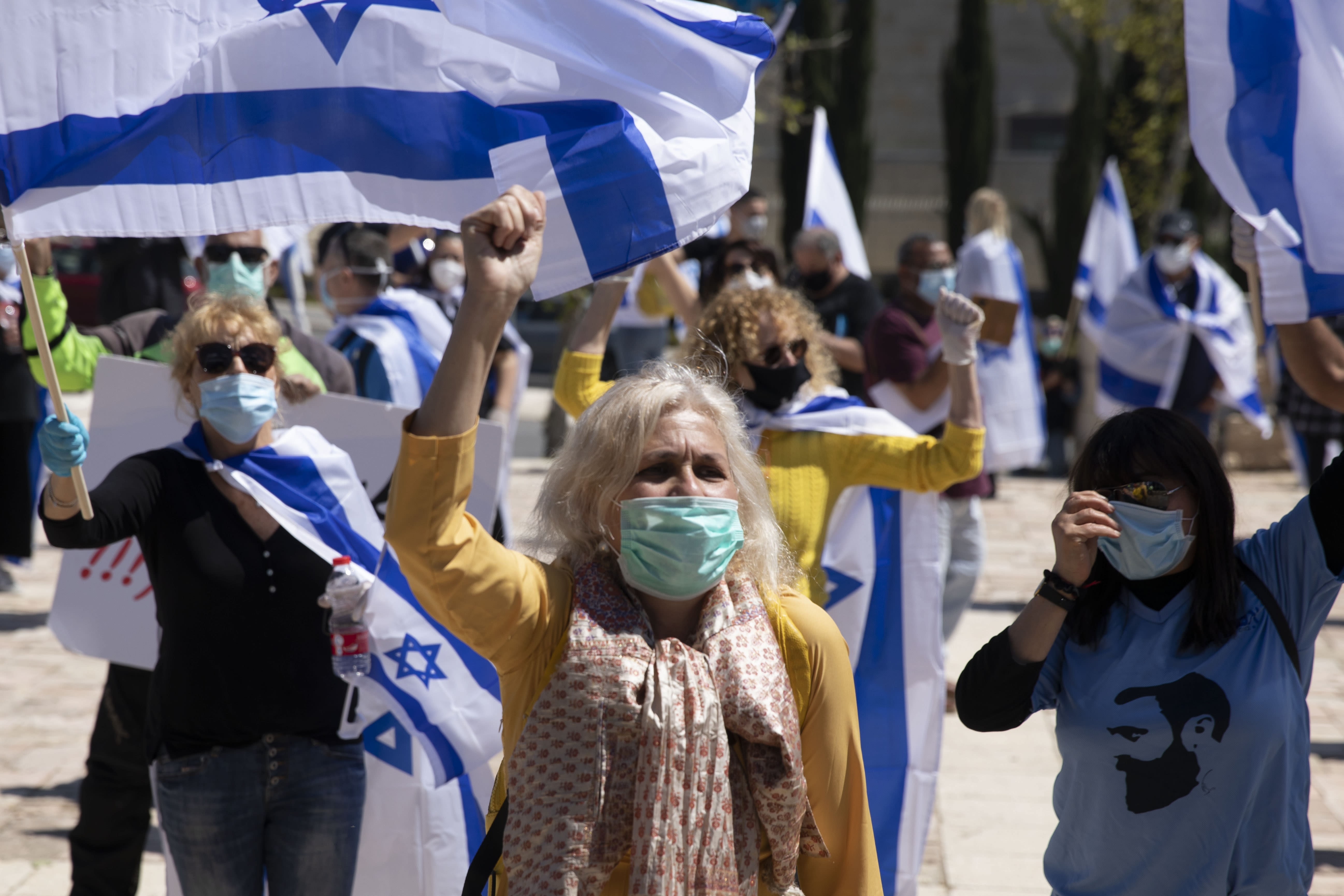 Protesters wearing masks amid concerns over the country's coronavirus outbreak hold Israeli flags and shout slogans during a protest by supporters of Prime Minister Benjamin Netanyahu in front of Israel's Supreme Court in Jerusalem, Thursday, April 30, 2020. Dozens of protesters rallied outside Israel's Supreme Court on Thursday against petitions to disqualify Benjamin Netanyahu from serving as prime minister while facing criminal indictments. (AP Photo/Ariel Schalit)